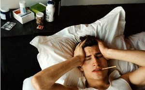 Teenage boy (17-19) in bed with thermometer in mouth holding head
