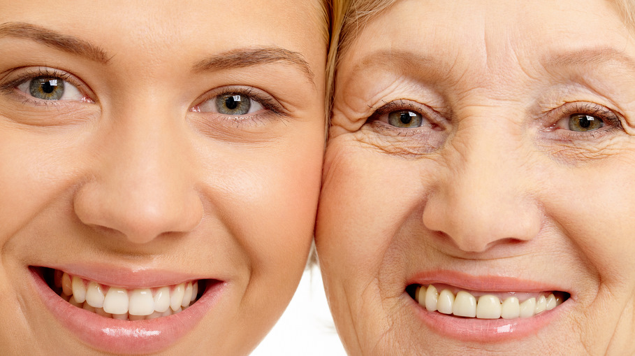 an older mother and young adult daughter are cheek to cheek and smiling at the camera