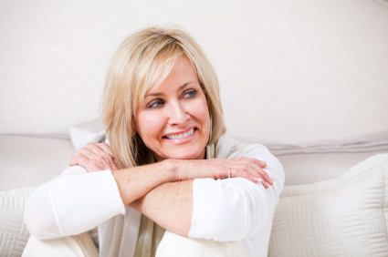 a smiling 50-year-old blonde woman dressed in white and sitting on a white couch