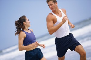 a physically fit  young man and woman run on the beach